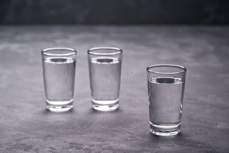 Trois tirs de vodka sur la table noire, l'espace de copie image libre de droits