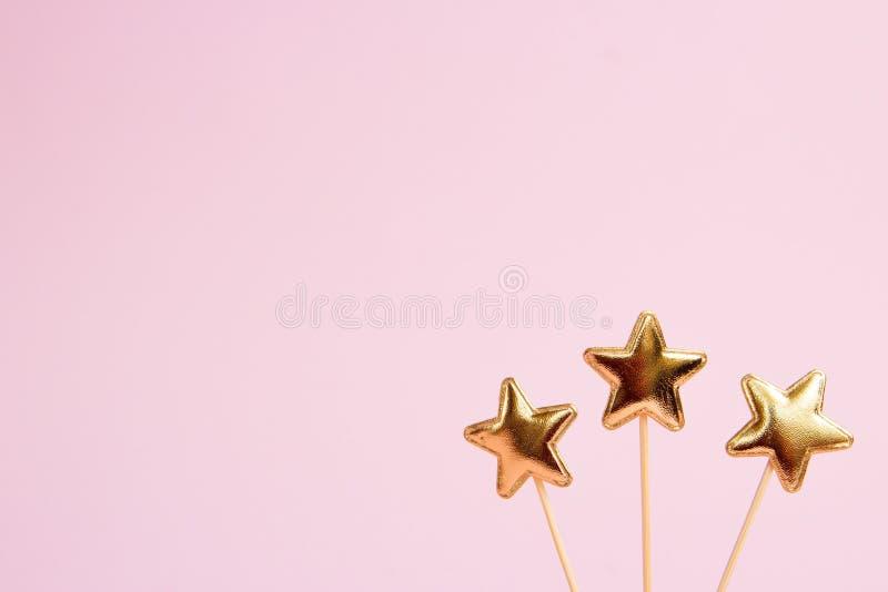 Trois ?toiles brillantes sur un fond rose D?corations pour la f?te de vacances Copiez l'espace photographie stock libre de droits