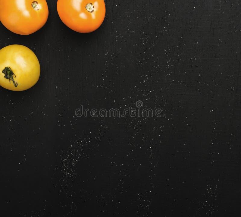 Trois tomates juteuses en haut de l'image sur le fond texturisé noir Légumes frais pour la consommation photographie stock
