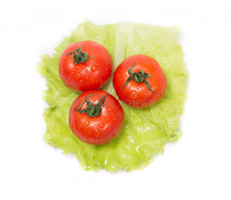Trois tomates se trouvant sur une feuille de salade verte photographie stock