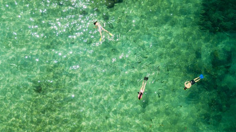 Trois touristes nageant dans l'eau de turquoise images libres de droits