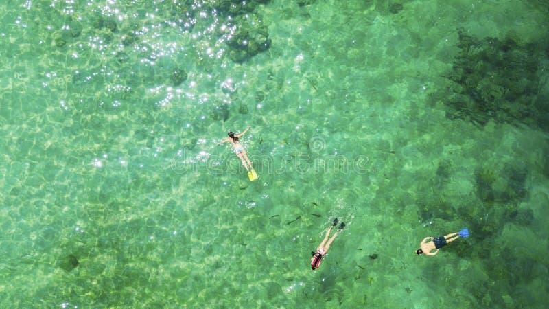 Trois touristes naviguant au schnorchel dans l'eau de turquoise images stock