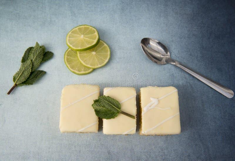 Trois tranches de gâteau de citron avec des chaux et des feuilles en bon état photos stock