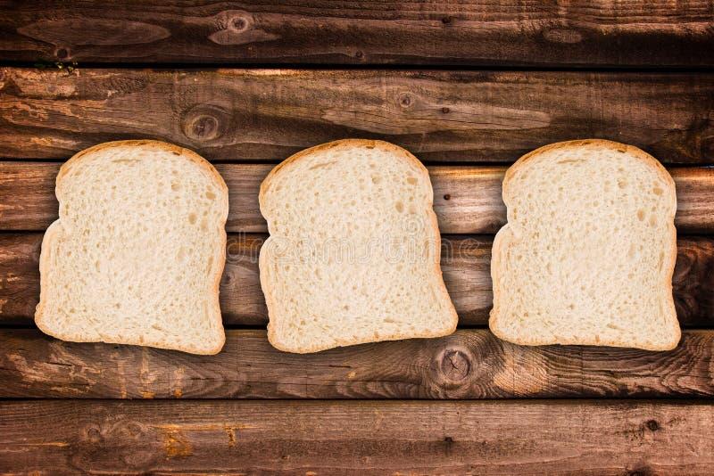 Trois tranches de pain, sur les planches en bois photo libre de droits