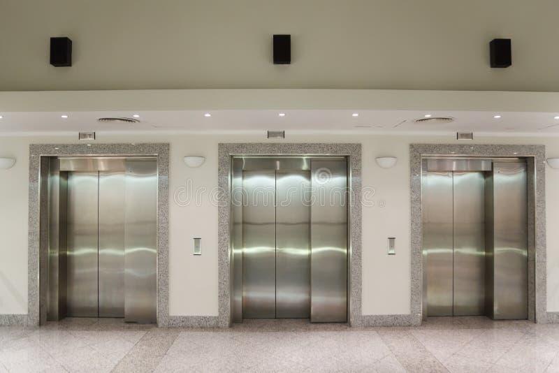 Trois trappes d'ascenseur dans le couloir photo libre de droits