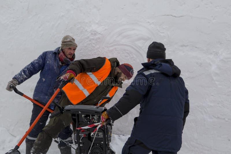 Trois travailleurs dans une tempête de neige pendant le déblaiement de neige photos libres de droits