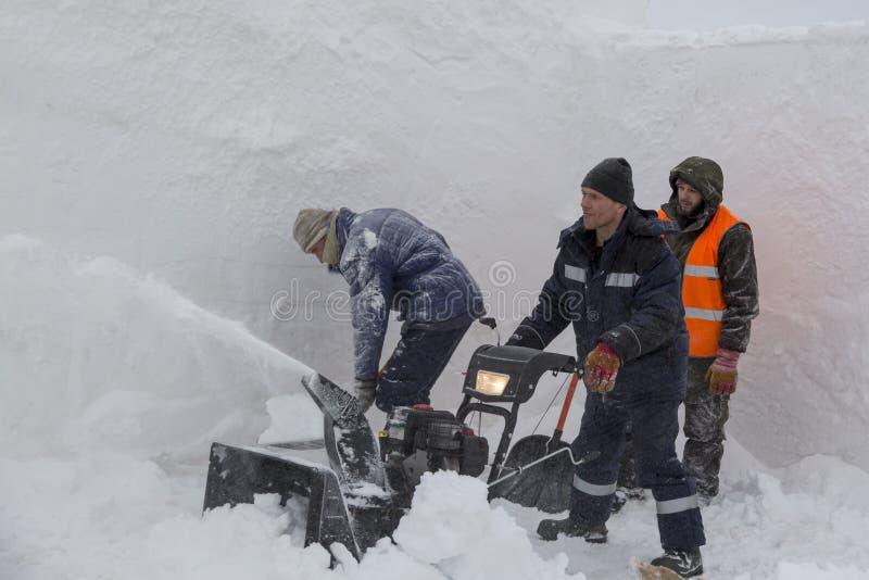 Trois travailleurs dans une tempête de neige pendant le déblaiement de neige photographie stock libre de droits