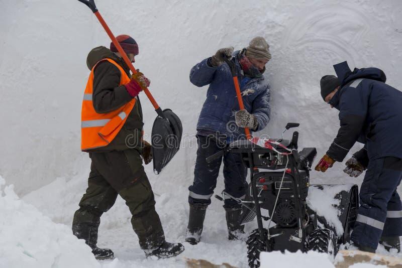 Trois travailleurs dans une tempête de neige pendant le déblaiement de neige photographie stock