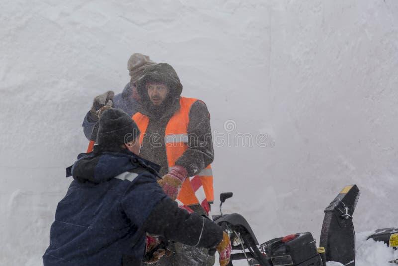 Trois travailleurs dans une tempête de neige pendant le déblaiement de neige images libres de droits