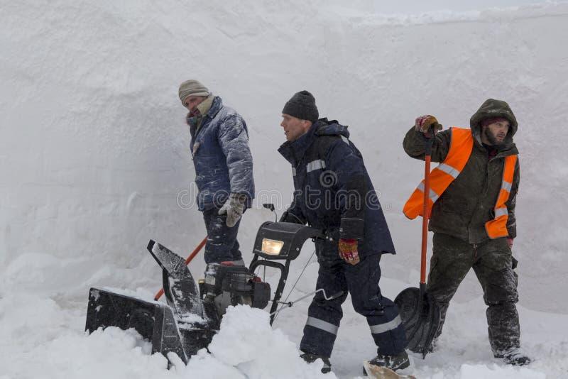 Trois travailleurs dans une tempête de neige pendant le déblaiement de neige photo libre de droits