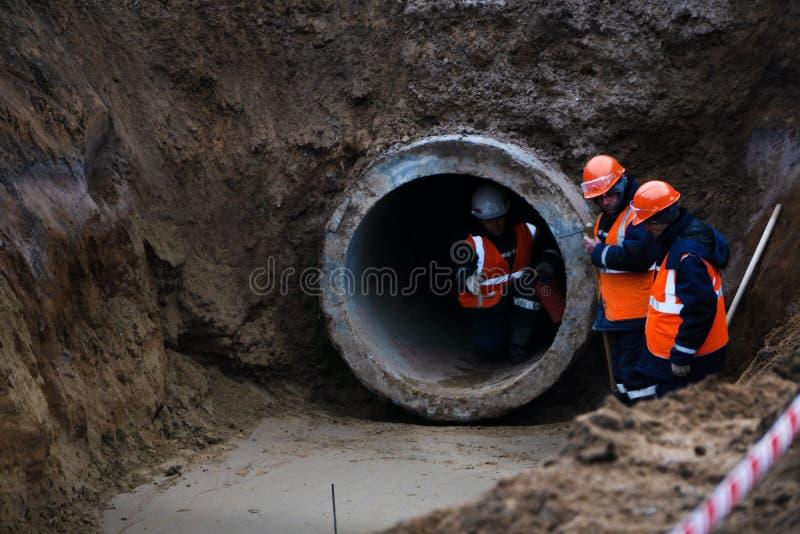Trois travailleurs installent les gouttières concrètes du côté de la route, centrales Vue soulevant le tuyau concret de drainage  image stock