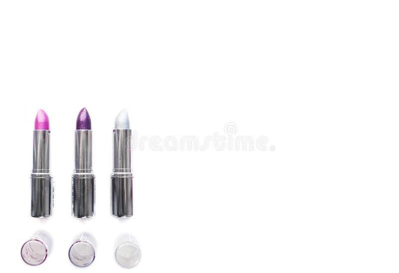 Trois tubes métalliques argentés ouverts de pourpre rose et d'argent de rouge à lèvres d'isolement sur le fond blanc maquillage d images stock
