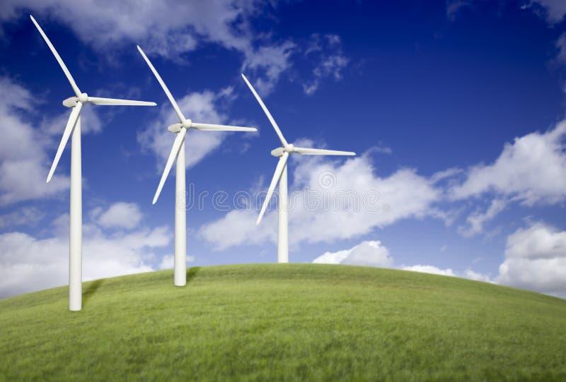 Trois turbines de vent au-dessus de zone d'herbe et de ciel bleu photo libre de droits