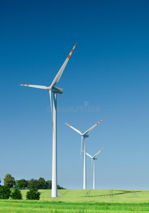 Trois turbines de vent sur la zone verte photographie stock