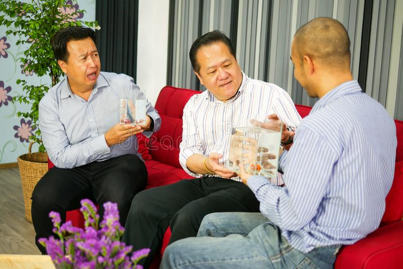Trois types asiatiques voient des poissons de betta dans le verre et le sentiment très heureux images stock