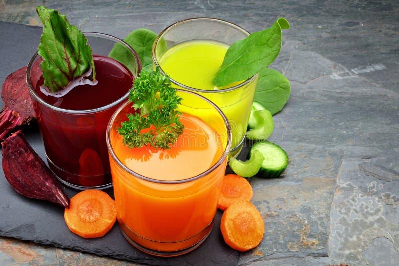 Trois types de jus de légumes organique avec des ingrédients sur l'ardoise photographie stock