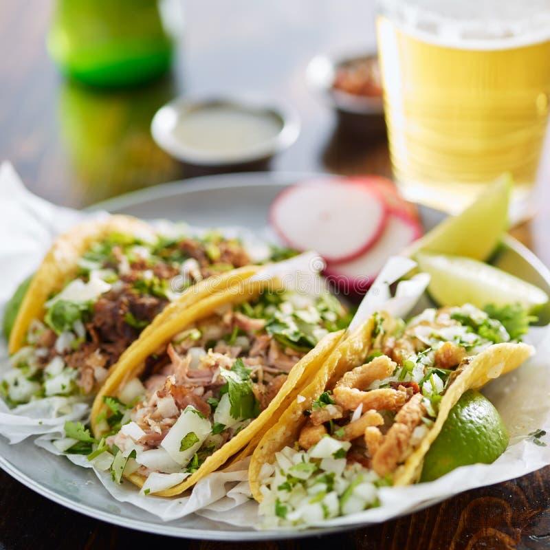 Trois types de tacos mexicains de rue avec le barbacoa, les carnitas et le ³ n de Chicharrà image stock
