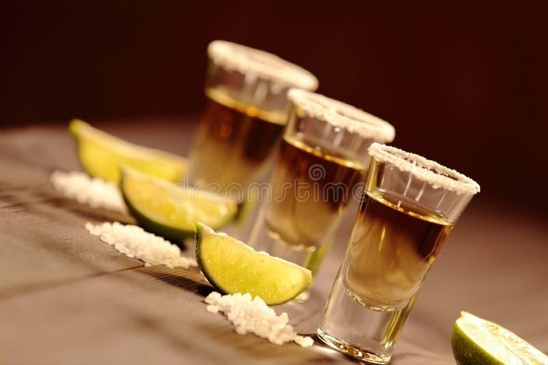 Trois verres courts avec de l'alcool à côté d'une tranche de chaux et de sel sont sur une vieille table rustique avec la texture  photographie stock