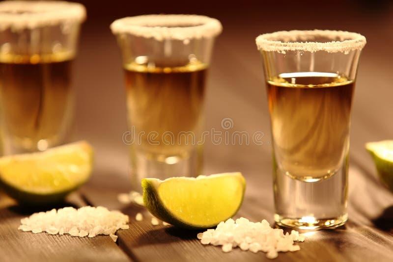 Trois verres courts avec de l'alcool à côté d'une tranche de chaux et de sel sont sur une vieille table rustique avec la texture  images stock