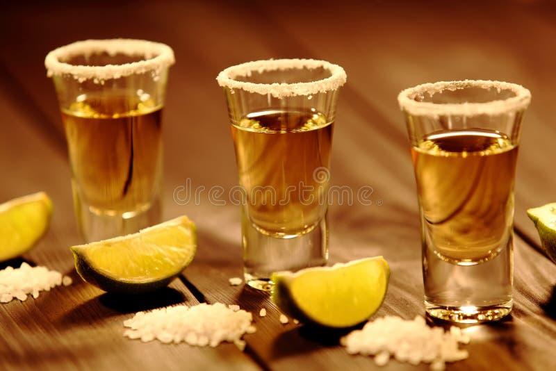 Trois verres courts avec de l'alcool à côté d'une tranche de chaux et de sel sont sur une vieille table rustique avec la texture  photos libres de droits