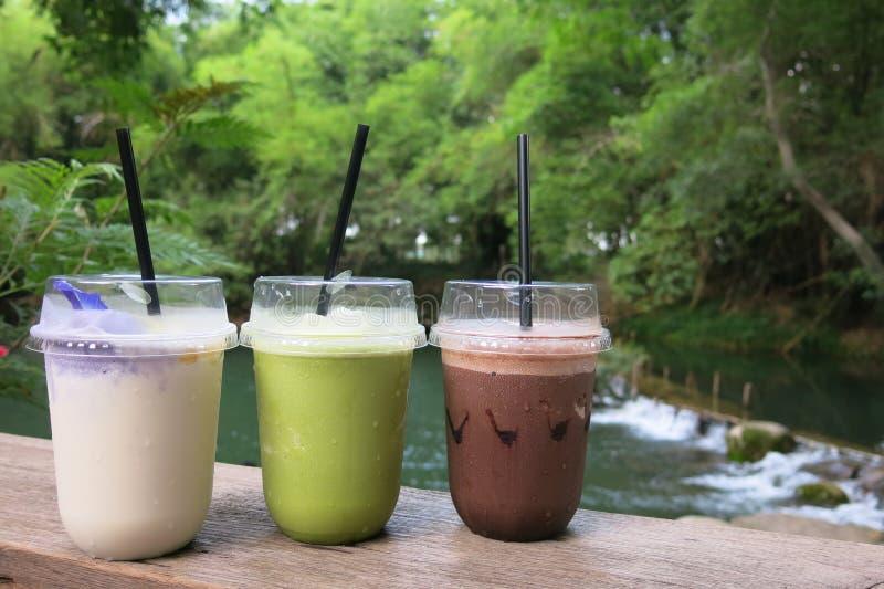 Trois verres de boisson - cacao, thé vert et jus glacés de noix de coco de milk-shake image stock