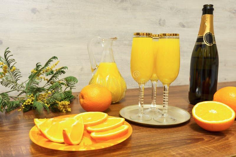 Trois verres de cocktail de mimosa, une bouteille de champagne, un décanteur avec le jus d'orange, oranges fraîches, brin de mimo photo libre de droits