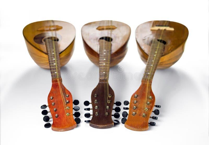 Trois vieilles mandolines ont tourné des touches jusqu'à la caméra D'isolement sur un fond blanc image libre de droits