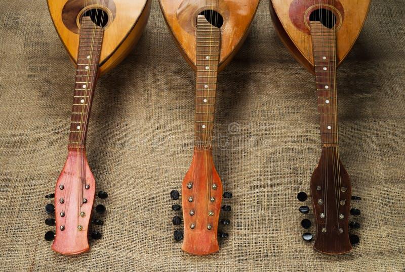 Trois vieilles mandolines ont tourné des touches jusqu'à la caméra sur un fond de toile de jute rugueuse photographie stock