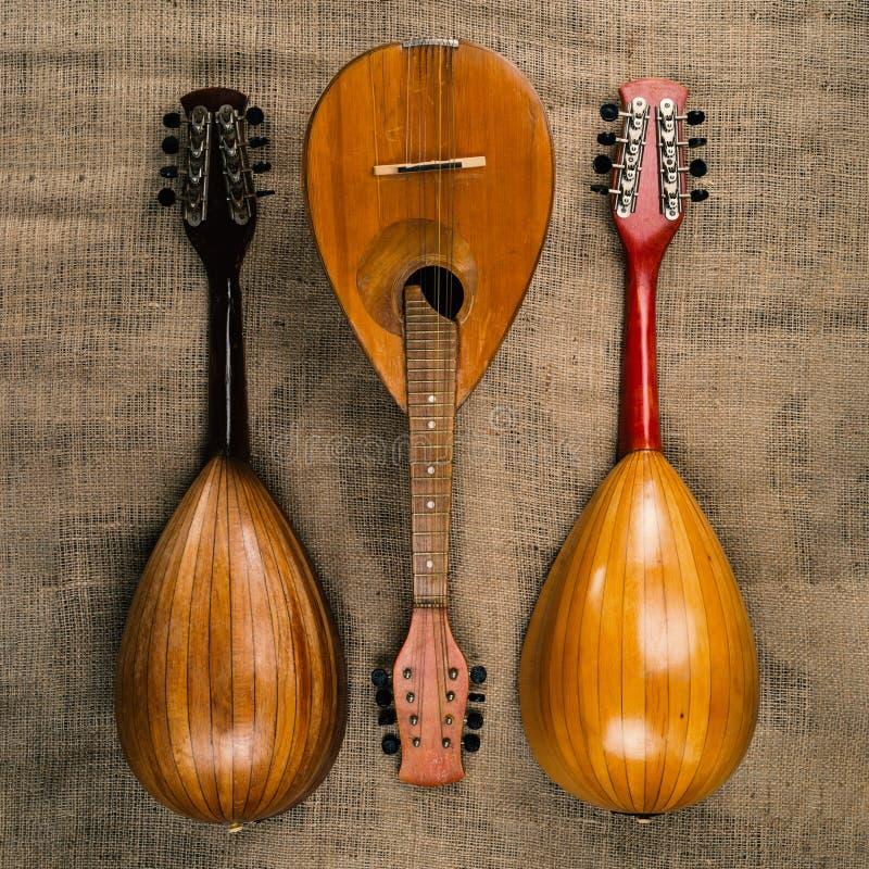 Trois vieilles mandolines sur un fond de texture approximative de toile de jute photo stock