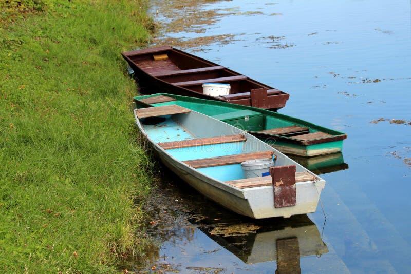 Trois vieux vieux bateaux en bois fortement utilisés attachés à la berge entourée avec la rivière calme et l'herbe non coupée images stock