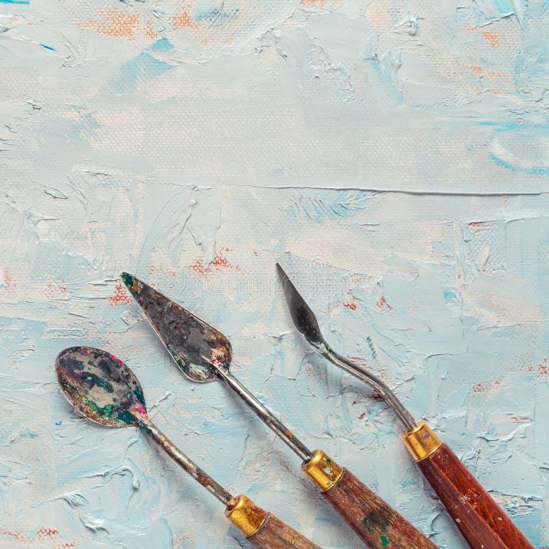Trois vieux couteaux de palette sur la toile d'artiste image libre de droits