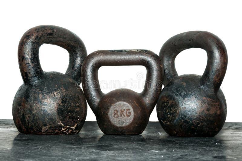 Trois vieux et cloches de bouilloire de rouille sur le plancher de gymnase photographie stock libre de droits