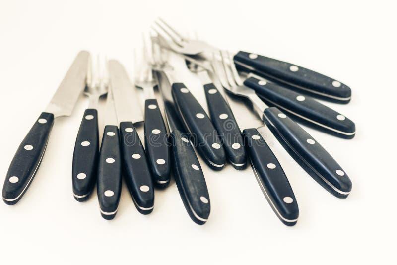 ?troitement vers le haut de six couteaux et fourchettes d'isolement sur le fond blanc photos stock