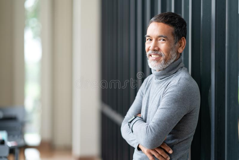 Trok de portret aantrekkelijke rijpe Aziatische mens zich met modieuze korte baard terug glimlachend bij koffiewinkel openlucht stock fotografie