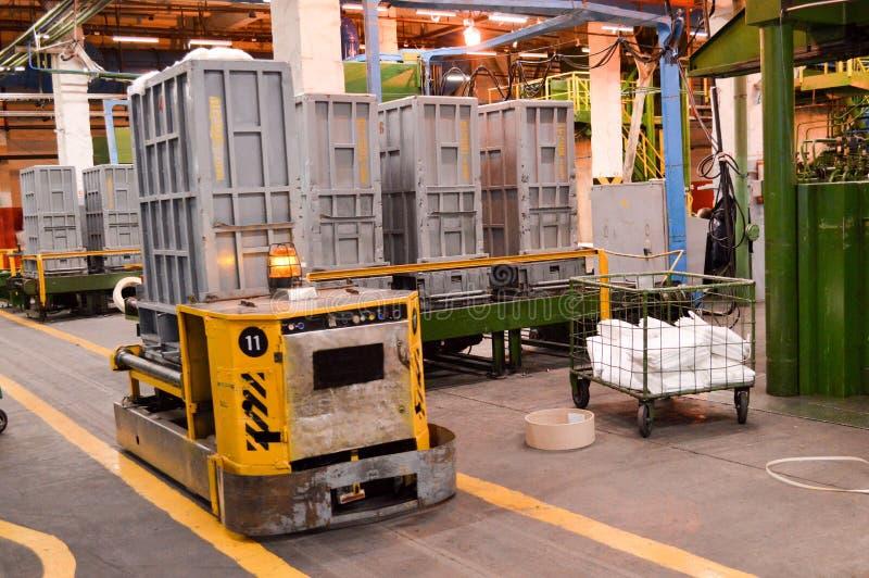 Trole automotor, autônomo do metal amarelo, máquina com sinalização da luz de emergência para o transporte de bens no productio imagens de stock