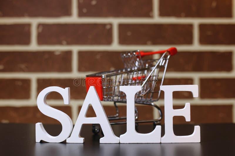 Trole para produtos em uma venda do ` s do ano novo do fundo da parede de tijolo fotografia de stock royalty free