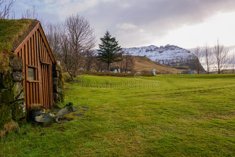 A Troll House In Iceland On A Green Meadow With Snowy Mountains In The Background stock photo