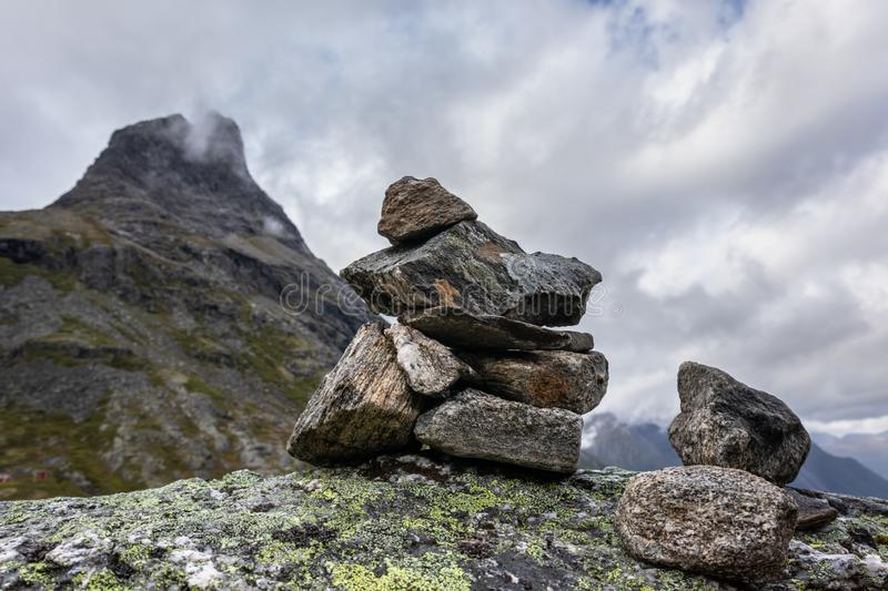 Troll rock pyramid with rainbow on top of Trollstigen road. Stone cairn. Among a mountain landscape in Norway royalty free stock photos