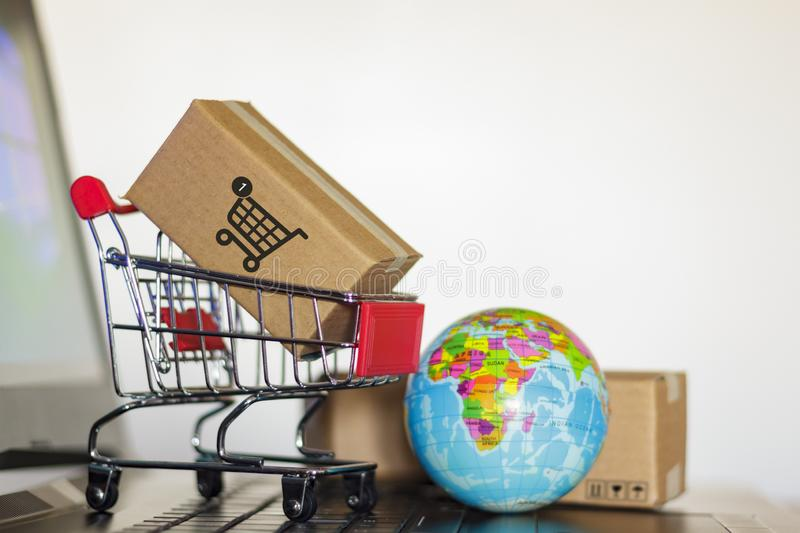 Trolley with boxes and earth globe on computer. Online shopping, e-commerce and worldwide delivery business concept stock photo