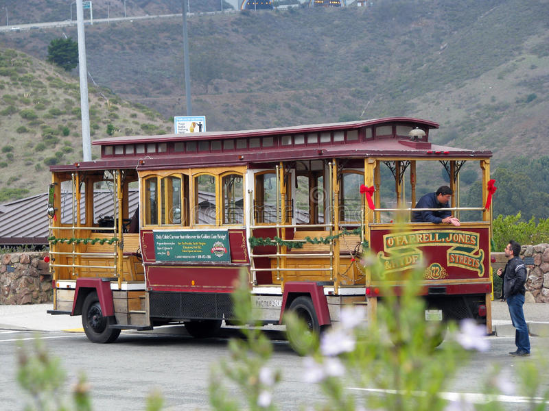 Trolley car. Red and gold trolley car with conductors in parking lot stock photo