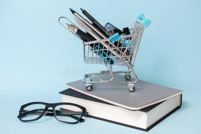 Trolley with different supplies with books and glasses on blue background. Education, Back to School, Shopping. royalty free stock photos