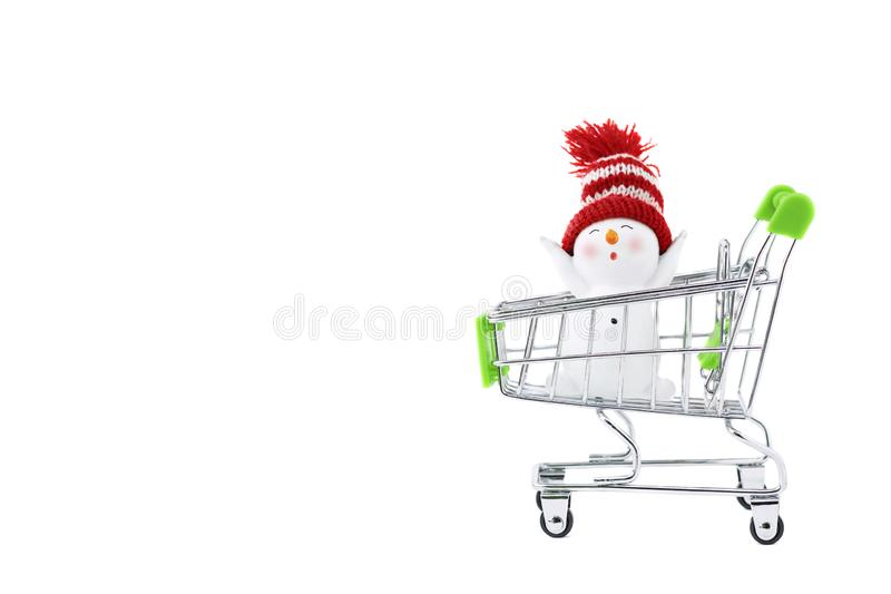 A trolley with a with happy joyful Christmas snowman. Isolated objects: toy snowman in a shopping cart, on white background, royalty free stock images