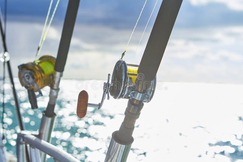 Trolling fishing boat rod and golden saltwater reel deep blue ocean sea wake. Dominican Republik Punta Cana Fishing boat stock photo