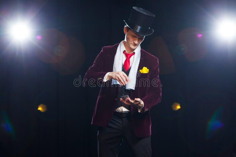Trollkarl jonglörman, rolig person, svart magi, trick för illusionmanvisning med kort fotografering för bildbyråer