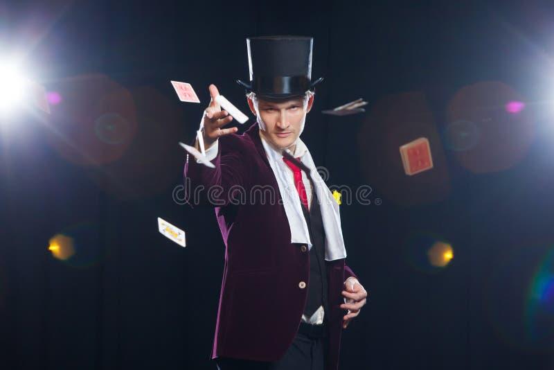 Trollkarl jonglörman, rolig person, svart magi, trick för illusionmanvisning med kort kastade kort royaltyfri fotografi
