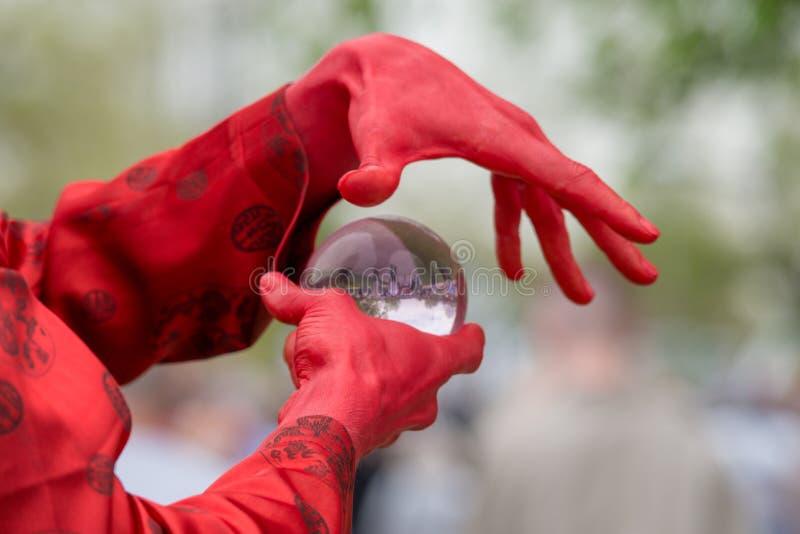 Trollkarlen i dolt i röd kroppmålarfärg gjuter ett pass genom att använda en glass sfär arkivfoto