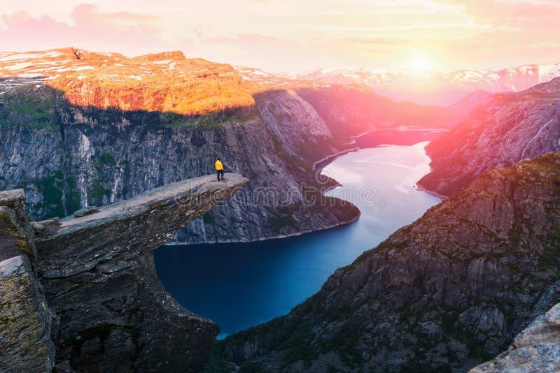 Trolltunga岩石的单独游人 免版税库存图片