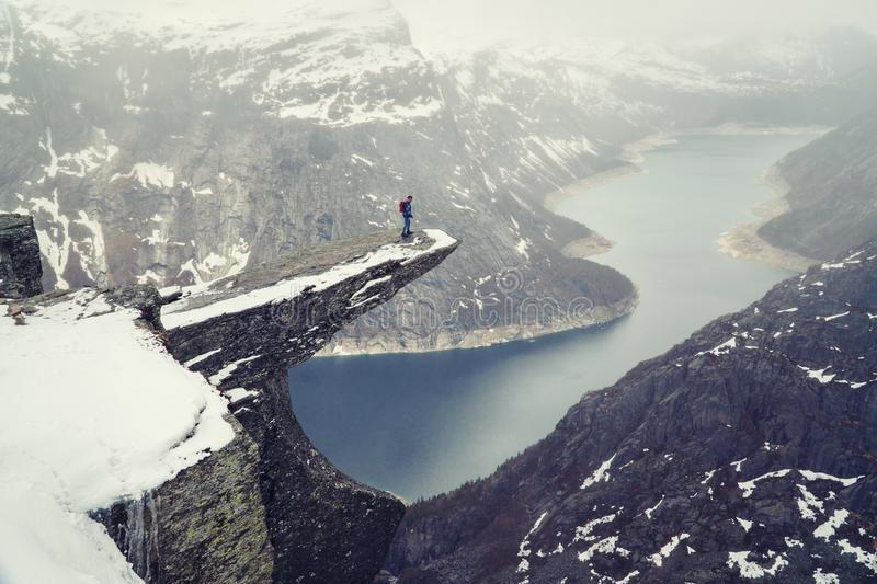 Trolltunga cliff under snow in Norway. Scenic Landscape. Man traveller standing on edge of rock and looking down. Travel stock photography