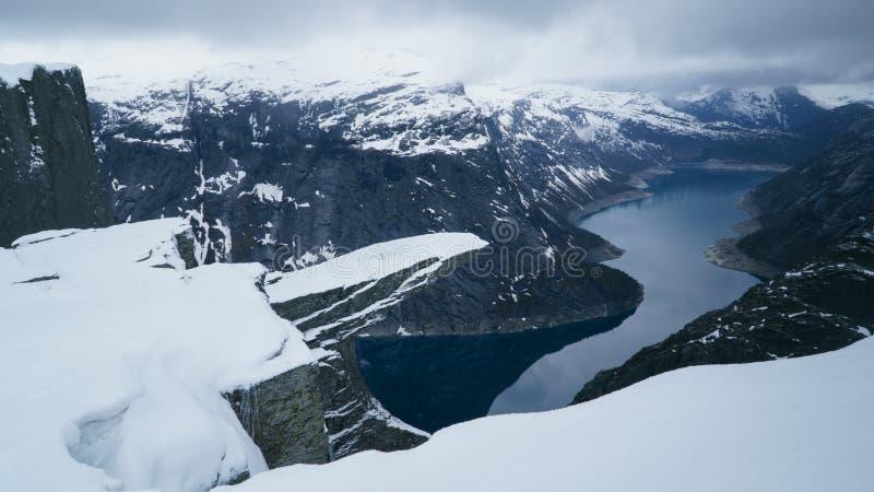 Trolltunga sob a neve, paisagem da língua da pesca à corrica, formação do inverno de rocha no Hardangerfjord perto da cidade de O foto de stock royalty free