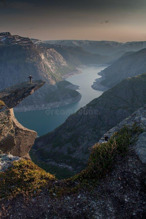 Trolltunga (trolls tunga) - man anseendet på vagga ovanför sjön royaltyfri foto